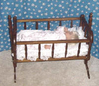 Lee Middleton doll in wooden baby doll cradle